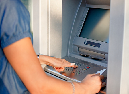 Photo pour Woman using ATM holding card and pressing the PIN security number on the keyboard automatic teller machine - image libre de droit