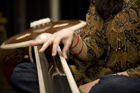 An Indian Musican plucks a string on a Tabla