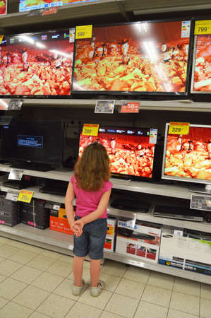 Television store - Cute little girl looks at plasma TVs in hypermarket
