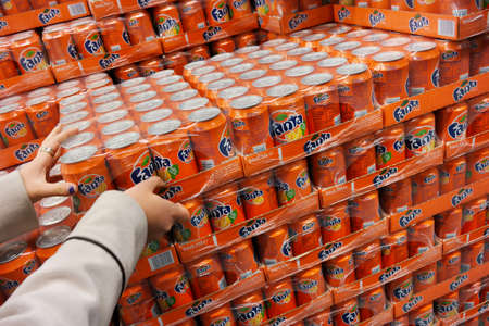 THE NETHERLANDS - MARCH 2015: Stack of with 24-packs of shrink wrapped Fanta cans in a wholesale.  Fanta is a global brand of fruit-flavored carbonated soft drinks created by The Coca-Cola Company.
