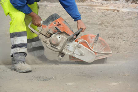 Construction worker operated Circular saw with a diamond blade for cutting asphalt and concrete.