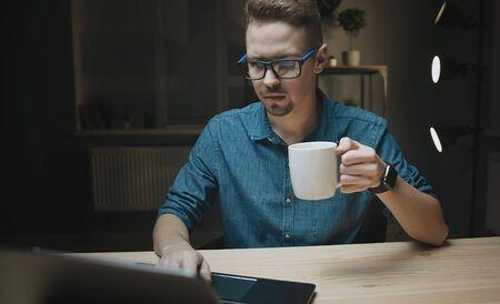 Photo pour Man holding cup looking at laptop - image libre de droit