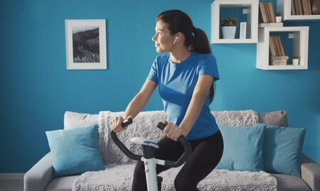 Photo pour Sporty happy girl training on exercise bike at home listening music looking aside, healthy life - image libre de droit