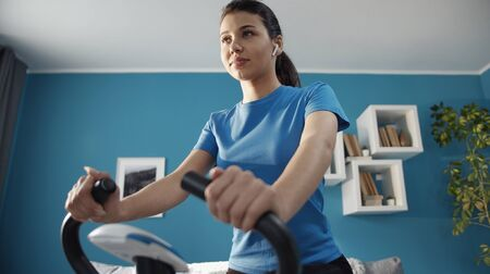 Photo pour Athletic girl exercising on stationary bicycle in flat listening music in earbuds, bottom up shot - image libre de droit