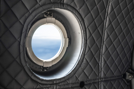Interior of military plane. View through the window during the fly. War and conflict conception.