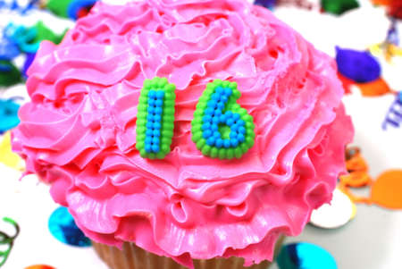 Number 16 celebration cupcake with confetti.