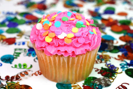 Celebration cupcake with confetti in background.