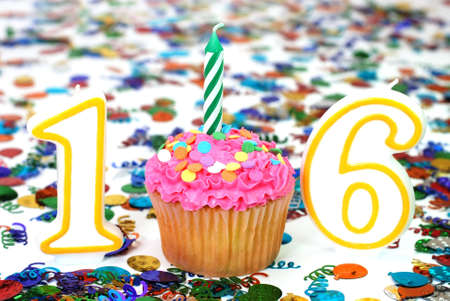 Number 16 celebration cupcake with candle and sprinkles with confetti in background.
