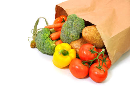 Foto de Vegetables in grocery bag isolated on white background. - Imagen libre de derechos