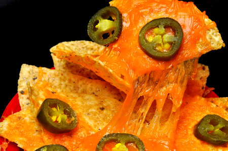Closeup of nachos with jalapeno pepper slices.  Isolated on black background.