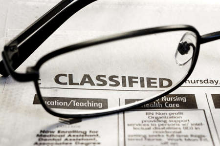 Closeup of classified ads in newspaper with reading glasses.
