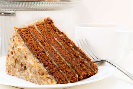 Slice of german chocolate cake closeup with cup of coffee.  Isolated on white background.