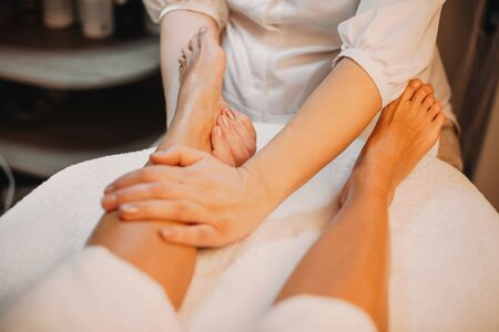 Caucasian masseur softens the client's feet before proceeding to the next procedure