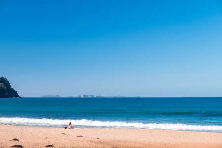 Foto de A bikini girl doing meditation and enjoying next to the ocean. Peaceful concept.. - Imagen libre de derechos