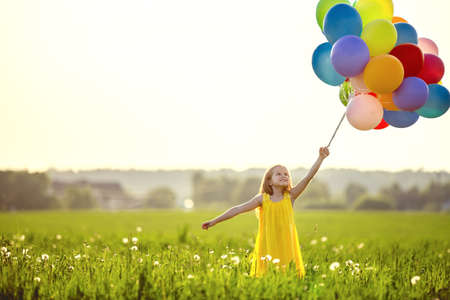 Photo pour Little girl with balloons in the field - image libre de droit