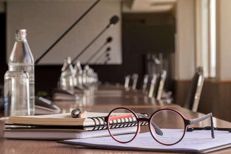 Photo pour Glasses, pen, pencil, and notebooks in meeting room - image libre de droit