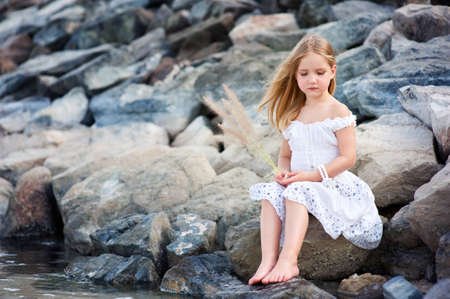 Lonely beautiful girl sitting on stone sea shore and thinking