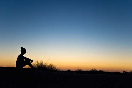 Silhouette of a woman sitting in the sunset