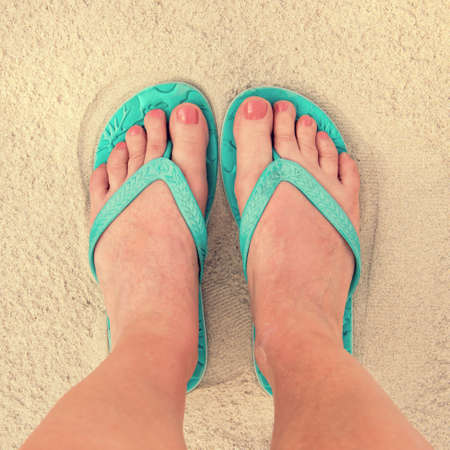 Photo for Selfie of woman feet wearing flip flops on a beach, vintage process - Royalty Free Image