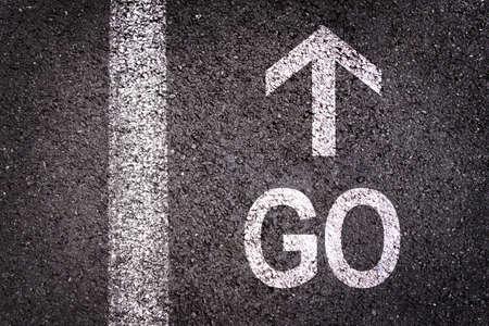 Word go and an arrow written on an asphalt road background