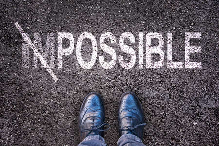 Photo pour Changing the word impossible on possible on an asphalt road with feet - image libre de droit