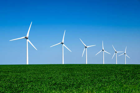 Photo pour Graphic modern landscape of wind turbines aligned in a green and yellow field - image libre de droit