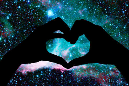 Foto de Hands in the shape of a heart, starry night background - Imagen libre de derechos