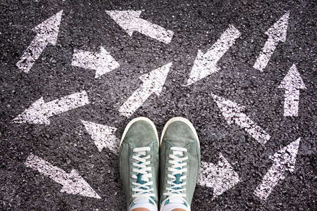 Foto de Sneaker shoes and arrows pointing in different directions on asphalt ground, choice concept - Imagen libre de derechos