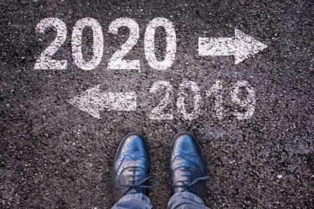 Foto für 2020 and 2019 with direction arrows written on an asphalt road background with legs - Lizenzfreies Bild