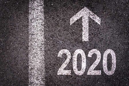 Photo pour 2020 and a direction arrow written on an asphalt road background, urban new year greeting card - image libre de droit