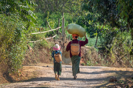Photo pour Woman and girl carrying heavy loads in Burma, Myanmar - image libre de droit