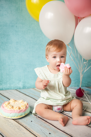 First birthday, baby girl with her birthday cake and colorful balloons, little girl licks a candle number one, happy birthday card