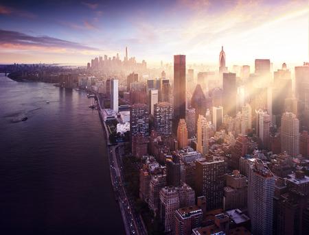 New York City - beautiful colorful sunset over manhattan fit sunbeams between buildings