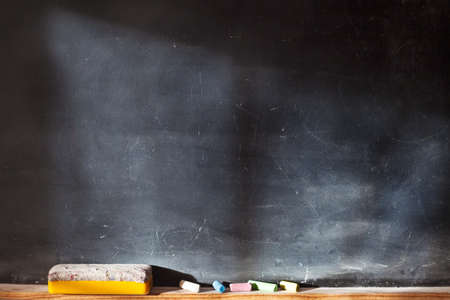 Photo pour Blank blackboard with colored chalks and eraser and light effect. Horizontal composition.  - image libre de droit