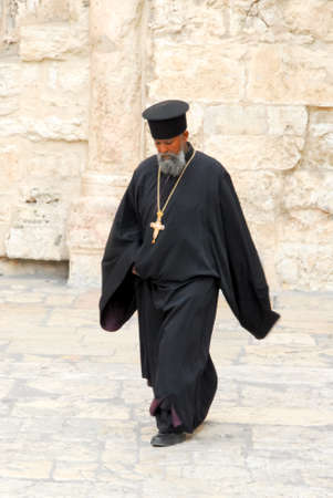 JERUSALEM, ISRAEL - JANUARY 20, 2007: Orthodox priest outside of the Holy Sepulchre Church. It is divided amongst six christian faiths.