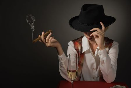 Portrait of beautiful woman in a black hat with a cigar