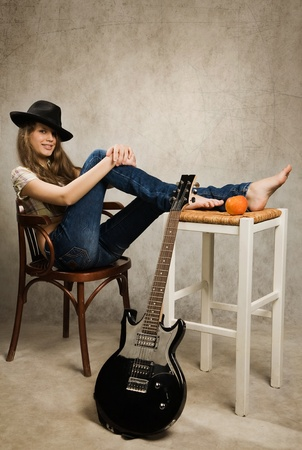 Barefooted teenager girl with electric guitar and apple