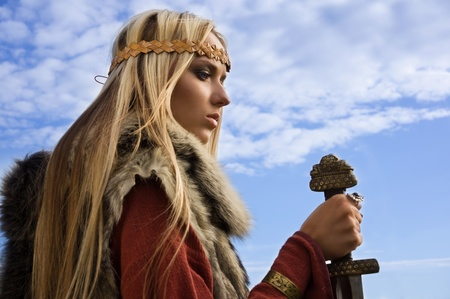 Portrait of the blonde girl in the Scandinavian suit with sword