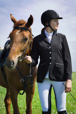 Beautiful young girl jockey with her horse dressing uniform competition