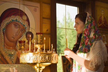 Russian woman with candles in Orthodox Russian Church