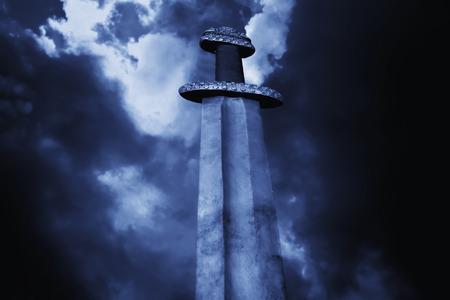 War symbol. Medieval viking sword against a dramatic sky