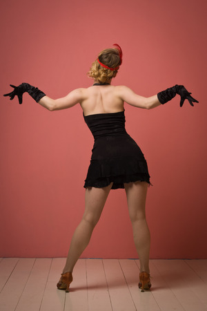 Gorgeous vintage 1920s lady dancing the charleston in a black dress with headband