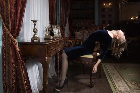 Photo pour Noir film. Sexual woman being strangled in a vintage interior - image libre de droit