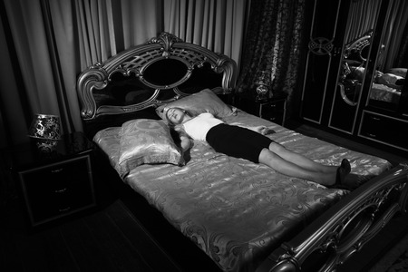Photo pour Strangled beautiful business woman in a bedroom. Simulation of the crime scene. - image libre de droit