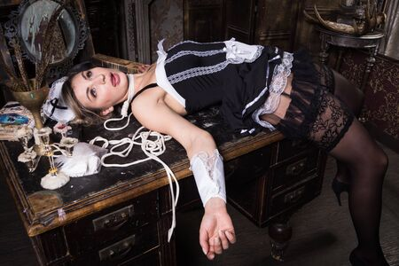 Photo pour Crime scene imitation. Strangled chambermaid lying on the table - image libre de droit