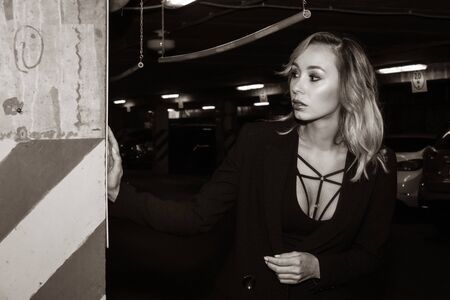 Photo for Noir film style woman in a black suit posing in an undergound car park - Royalty Free Image