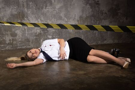 Photo for Crime scene imitation. Dead woman police officer lying on a floor - Royalty Free Image