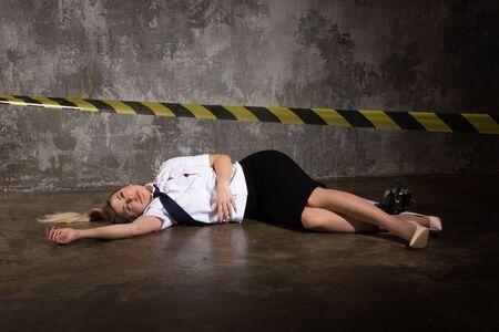 Foto de Crime scene imitation. Dead woman police officer lying on a floor - Imagen libre de derechos