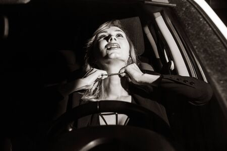 Photo for Scene from a detective series. Killer strangles business woman in her car. - Royalty Free Image