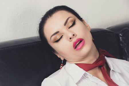 Photo for Crime scene (imitation). Strangled business woman lying on the couch - Royalty Free Image